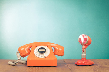 Retro red microphone and telephone front mint green background