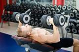 Muscular young man shirtless, training pecs on gym bench poster