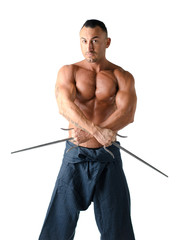 Muscular shirtless man with traditional martial arts daggers