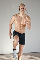 Young aerobics male coach shirtless teaching class