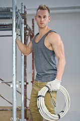 Handsome muscular manual worker holding cable hasp in hands