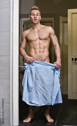 Shirtless muscular young male athlete in gym bathroom