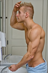 Muscular young man looking at his hair in bathroom mirror