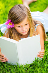 Cute little girl reading book outside on grass