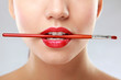 Woman's lips holding make up brush.
