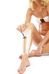 Shaving female legs, closeup, isolated on white