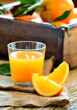 Glass of orange juice and fresh oranges