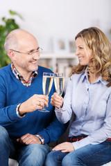 ehepaar prostet mit einem glas sekt