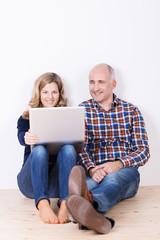 ehepaar sitzt mit laptop auf dem fußboden