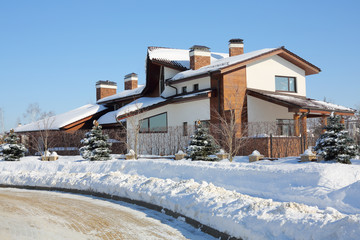 Beautiful two-storey house and trees on sunny frosty winter day.