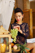 Pretty woman sits on bed and holds bunch of green grapes