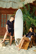 Man with surfboard looks at young woman sitting on wooden chair