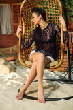 Beautiful young woman sits in wicker hanging chair