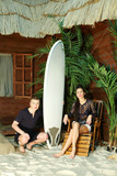 Man with surfboard hunkers and young woman sits on wooden chair