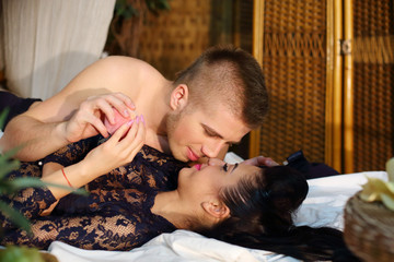 Beautiful woman and man lie on bamboo bed and touch each other