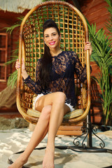 Happy young woman sits in wicker hanging chair