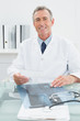 Smiling male doctor sitting at desk in office