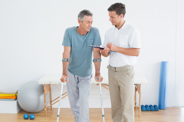 Therapist discussing reports with a disabled patient