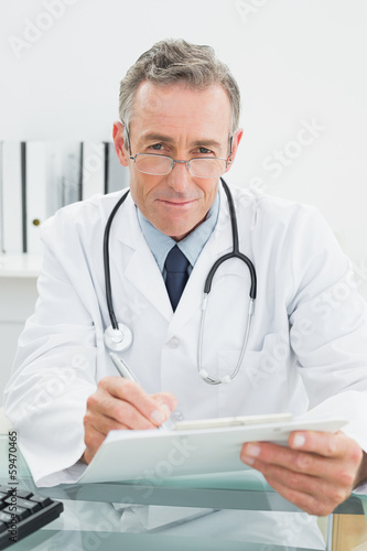 Portrait of a doctor writing a report at office