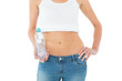 Mid section of a fit woman holding a bottle of water