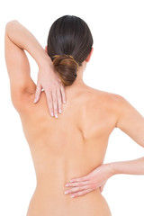 Rear view of a fit topless young woman with back pain