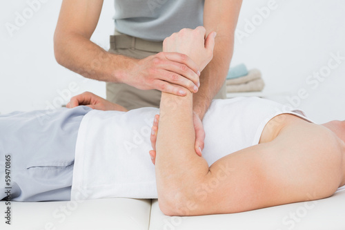 Mid section of a male doctor examining a patients hand