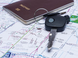 Key car and passport on map.