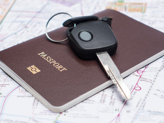 Key from the car and passport on map.