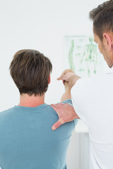 Rear view of a physiotherapist stretching a man's arm