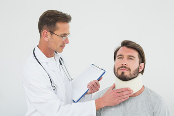 Male doctor examining a patient's sprained neck
