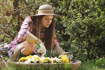 Beautiful gardener taking care of her flowers