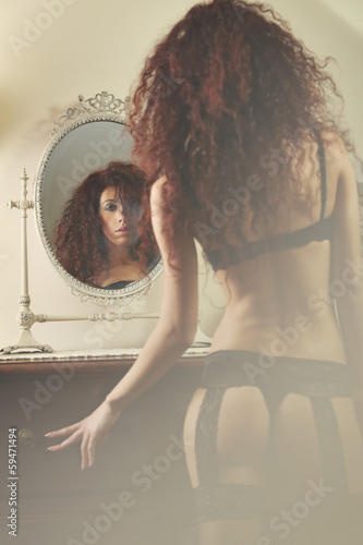 Mirror reflection of a beautiful woman in lingerie