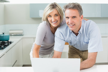 Portrait of a happy couple with laptop in kitchen