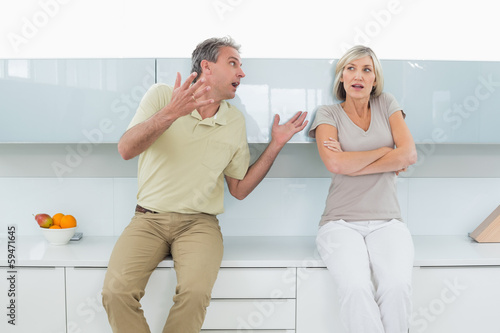 Woman with arms crossed as man argue in kitchen