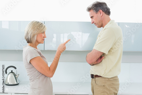 Angry couple arguing in kitchen