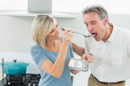 Loving woman feeding a man in kitchen