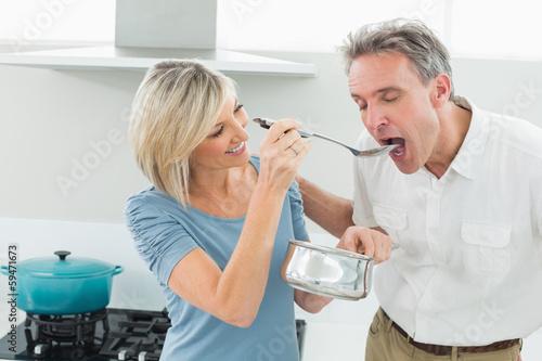 Loving woman feeding a man in kitchen