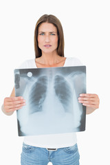 Portrait of a serious young woman holding lung x-ray