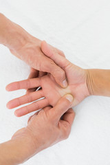 Doctor examining a female patient's palm