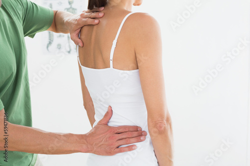 Physiotherapist examining woman's back in medical office