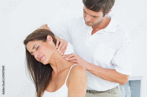 Male chiropractor massaging a young woman's neck Poster