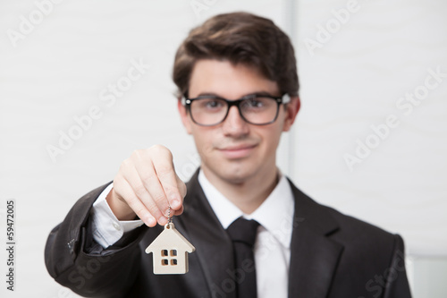 Young businessman giving house keys