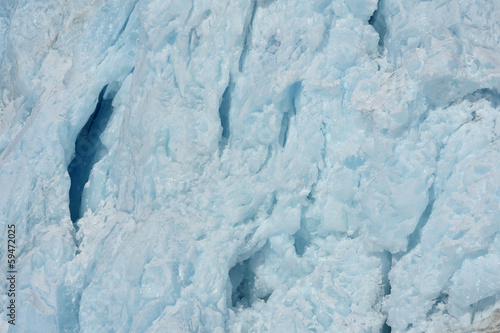 Detail front of a glacier ending in pack ice in sea.
