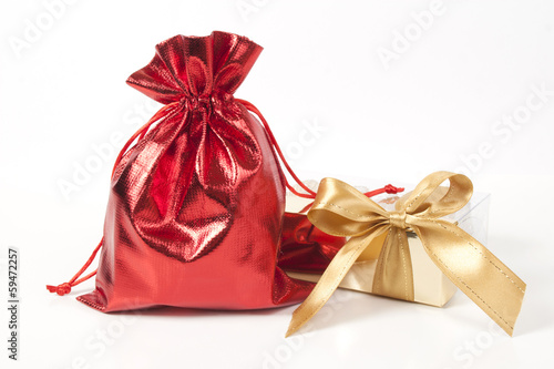 Red bag with gifts and a gold bow