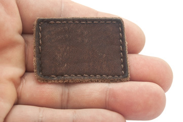 Blank leather label in a hand isolated over white