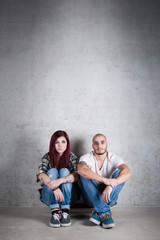 Couple portrait sit on skateboard against concrete wall.