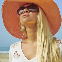 beautiful woman in hat on the beach.summer girl in sunglasses