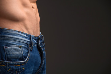 Close up of muscular male abdomen and blue jeans.