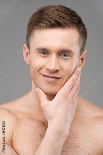 Portrait of handsome adult man touching unshaved face.