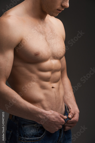 Close up of sexy fit man undressing.